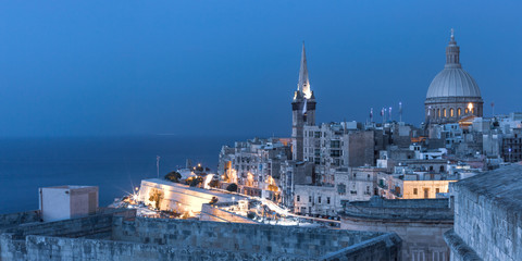 Wall Mural - View of Old town roofs, fortress, Our Lady of Mount Carmel church and St. Paul's Anglican Pro-Cathedral at night, Valletta, Capital city of Malta