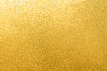 Gold wall texture background. Yellow shiny gold foil paint on wall surface with light reflection