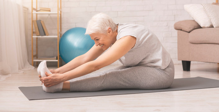 Active senior woman doing stretching exercises at home