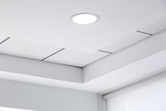 multi-level ceiling with three-dimensional protrusions and a suspended tiled ceiling with a built-in round led light in the corner of the room, close up details.