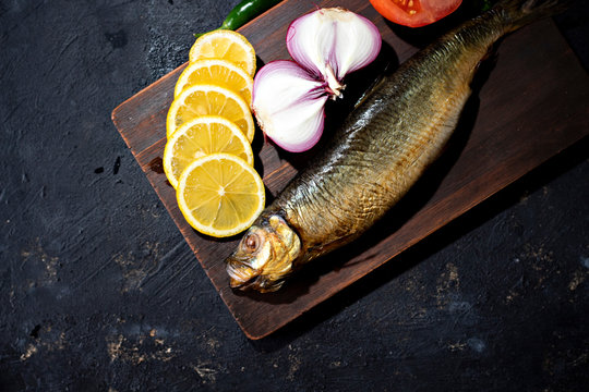 Kippers, smoked herring on a wooden board on ablack background, close up. Image