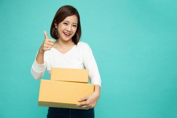 Happy Asian woman holding package parcel box and thumb up isolated on green color background, Delivery courier and shipping service concept