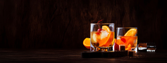 Alcoholic old fashioned cocktail with orange slice, cherry and orange peel garnish Wall mural