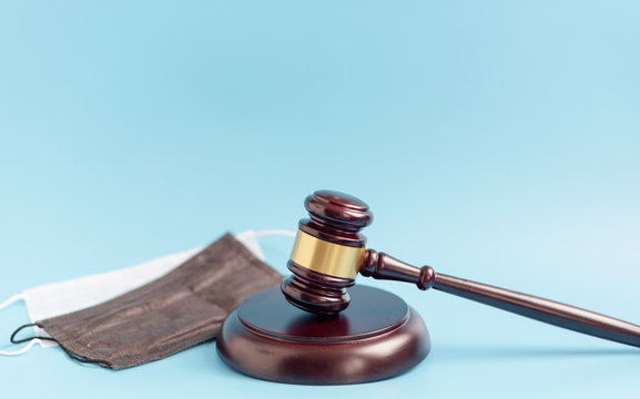 brown gavel and medical protective masks on a blue background