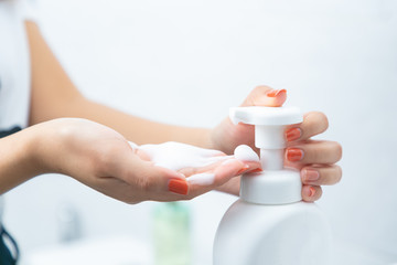 Woman hand press pure white plastic pump bottle and take cleaner foam.