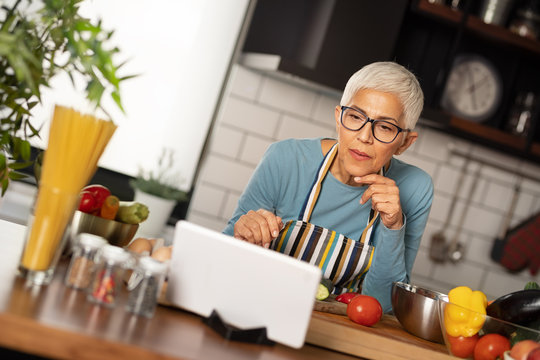 Looking for new recipes. Senior woman using digital tablet at kitchen