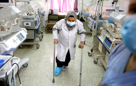 A nurse with a broken leg works in a room where premature babies are under control in incubators at a maternity hospital in Idlib