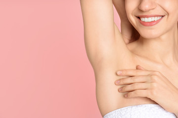 Young woman showing armpit with smooth clean skin on pink background, closeup. Space for text