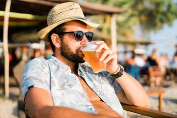 Young man drinking beer a beach bar enjoying sunset