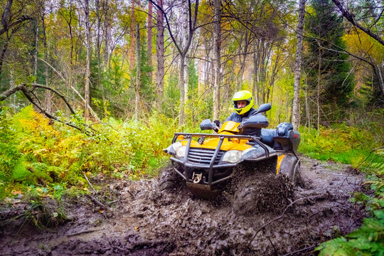 ATV. Man on a quad bike in the mud. The ATV overcomes dirt on the road. Yellow ATV in the forest. Concept - extreme sports. A man overcomes the terrain. Concept - quad bike store. Biker