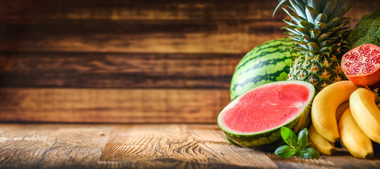 Tropical fruits on wooden background, many colorful fresh tropical fruits wide banner or panorama...