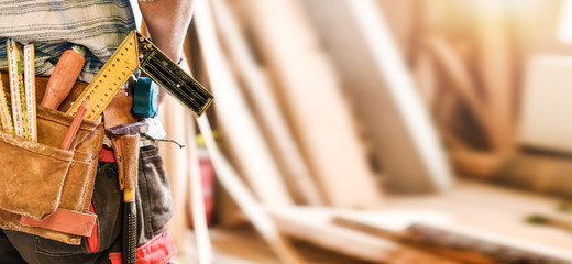 The carpenter with measuring and work tools in leather belt. Wide banner or panorama concept.
