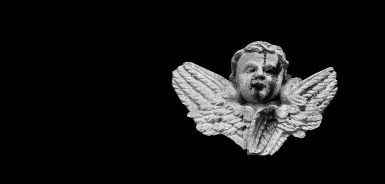 Close up of angel with wings. Vintage ancient stone statue isolated on black background