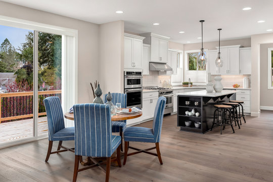 Kitchen and dining area in new luxury home. Features kitchen island, table with place settings, stainless steel appliances, and pendant lights.