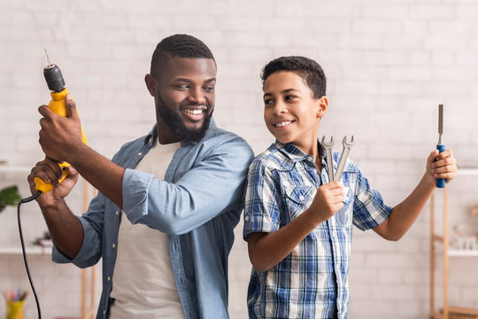 African Father And Son Standing Back To Back With Construction Tools