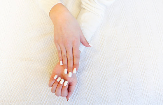 Crop woman showing white nails
