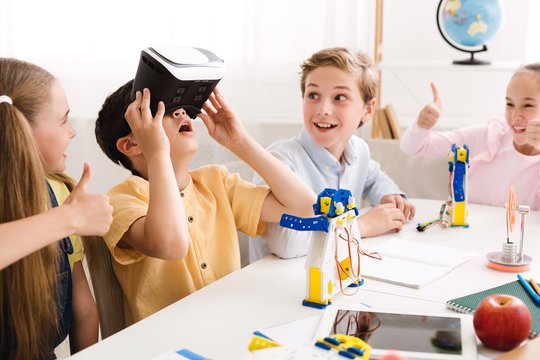 Happy school boy using VR glasses at technology lesson