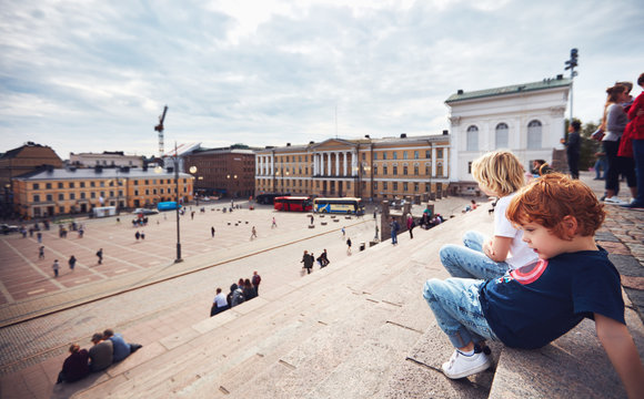 cute little tourists are relaxing on the step stairs of Helsinki Cathedral, on the Senate Square. Helsinki, Finland