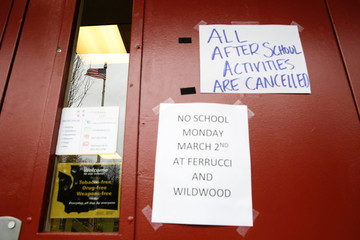 A US flag is reflected in a window as signs announcing a closure and cancelled activities are pictured at Ferrucci Junior High School after two schools were closed for cleaning due to flu-like symptoms of a relative in Puyallup