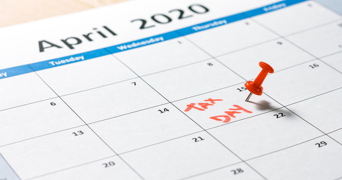 Writing and pinning tax day on calendar for april 15 with red color.