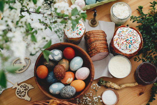 Easter food flat lay. Easter eggs natural dyed, easter bread, ham, beets, butter, green branches and flowers on rustic wooden table. Traditional Easter Food for breakfast