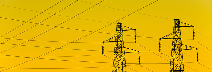 Electric power industry. Transmission towers or electricity pylons with golden sky background Wall mural