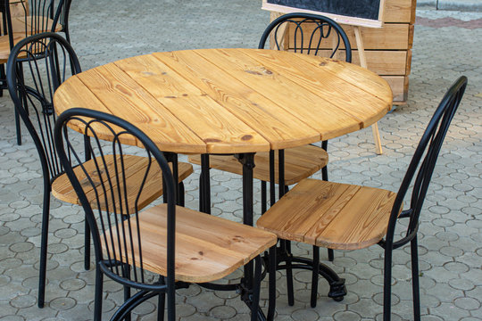 Wooden table with chairs for relax. Street cafe - tables and chairs stand on the street for food and snacks. Table and chair
