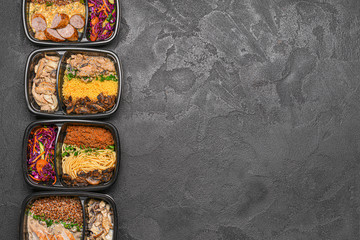Containers with healthy food on dark background