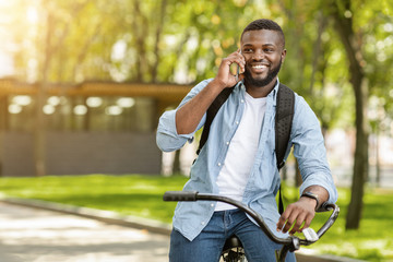 Smiling Black Guy Talking On Cellphone While Riding Bicycle Outdoors Papier Peint
