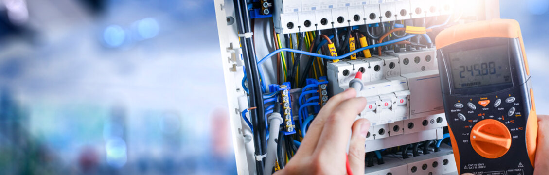 Electrician engineer installing and test electric connection wires of fuse switch box.