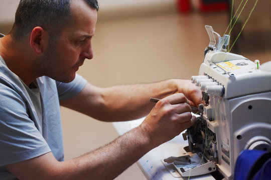 Repairman on factory repairs overlock machine sewing machine