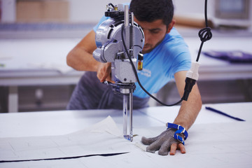 Young cutter on cloth textile factory works with cutting machine and iron glove
