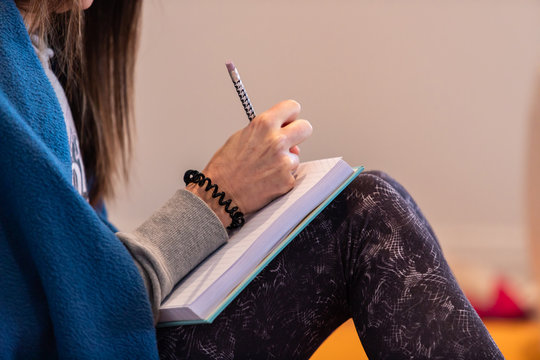 Close-up view of female hands making notes in the yoga class. Unrecognizable woman studying secrets of yoga poses. Side view