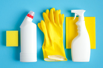 Set of cleaning supplies on blue background. Flat lay yellow rag and sponge, rubber gloves, cleaner spray bottle, detergent. House cleaning service and housekeeping concept