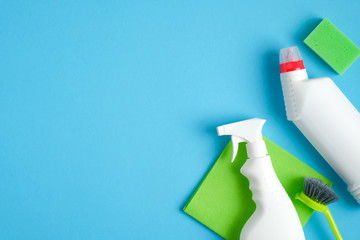Cleaning supplies on blue background. Top view cleaner spray bottle, green rag, sponge, detergent, brush, rubber gloves. House cleaning service and housekeeping concept