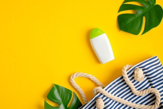Sunscreen cream lotion bottle mockup, striped beach bag and tropical leaves on yellow background. Summer sun protection concept. Flat lay, top view