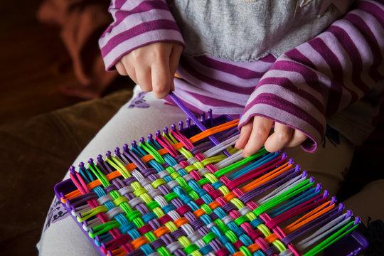 Child weaving potholder on plastic loom