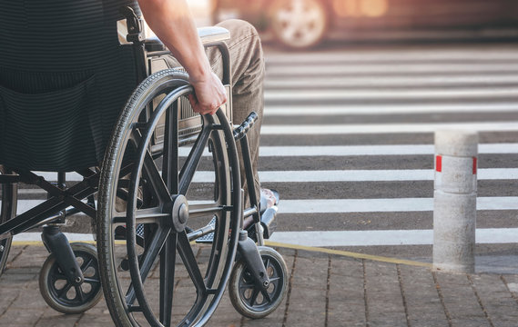 Disablee man on wheelchair crossing the road.