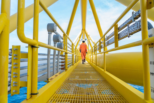 Production operator walking on offshore oil and gas central processing platform.