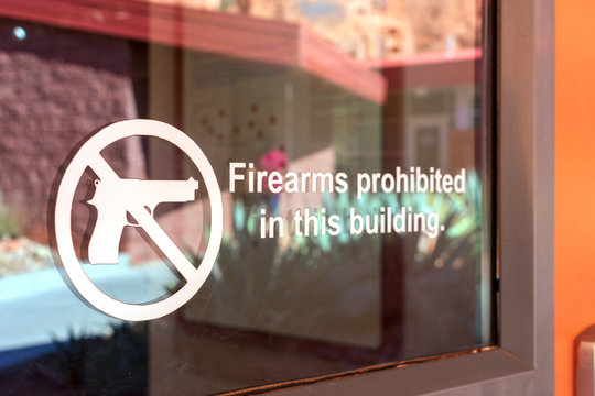 Firearms prohibited sign on the glass entrance door to establishment notifies patrons that weapons aren't allowed, and addresses security policy and protection concerns