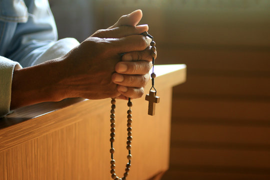Senior man kneel, holding wooden rosary beads in hand with Jesus Christ holy cross crucifix in the church. Natural light background. Prayer pose crop closeup with copy space. Catholic symbol of faith.