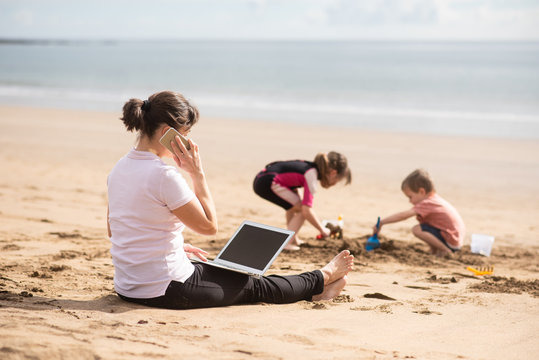 Woman attending phone call as kids go busy on the beach