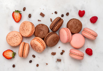 Spoed Foto op Canvas Macarons Composition with french macarons on white marble background. Top view of colorful pastel macaroons or macaron with berries, chocolate and coffee beans