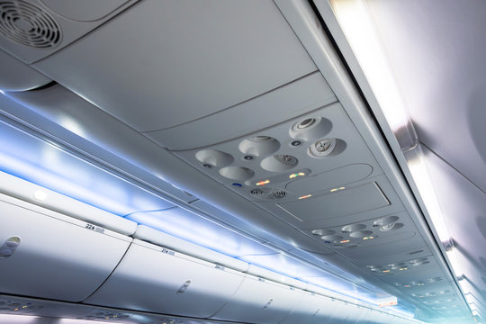 Overhead vents and lights along with luggage racks for hand luggage in an airplane.