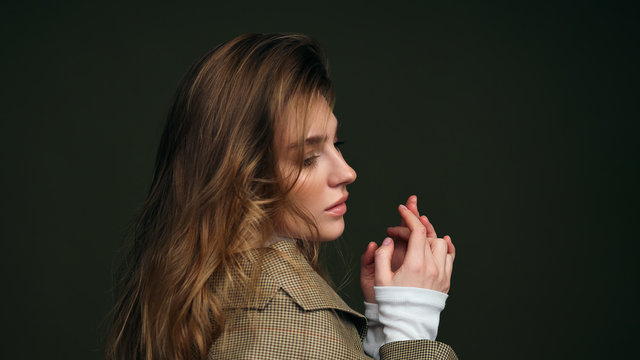 A young beautiful blonde woman in a white turtleneck and a man's jacket poses on a green olive background in the studio.