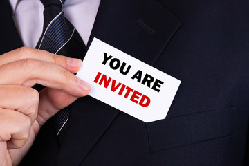 Businessman putting a card with text you are invited in the pocket