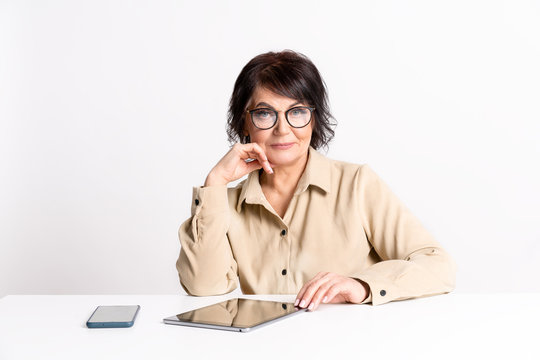 Beautiful Senior woman work at home in glasses and comfortable clothes by smartphone and tablet.