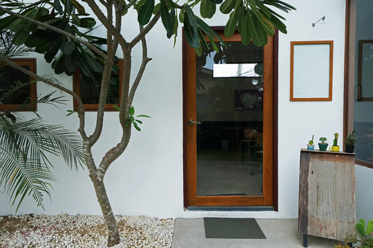 Exterior architecture and building design of coffee cafe and bakery shop decorated with wooden mirror glass frame and green plants