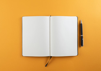 open diary or notebook with blank white pages on orange background template