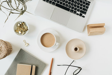 Home office desk workspace with laptop, coffee cup, notebook, glasses, pen, green plant branch on white background. Flat lay, top view girl boss work business concept for lifestyle blog, social media.